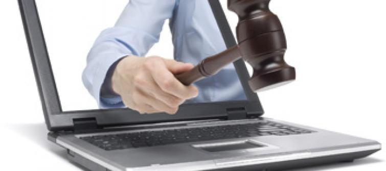 Auctioneer with gavel in laptop.