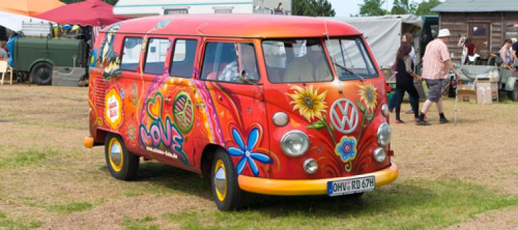 Image of a Volkswagon Van from the sixties with a flower power paint job.