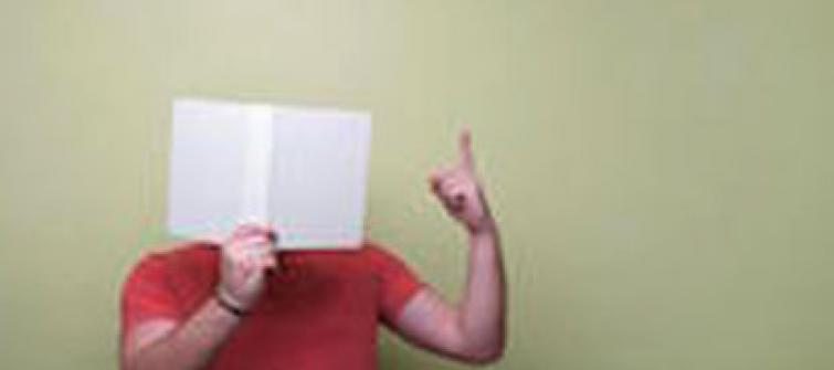 Man with a book in front of his face.