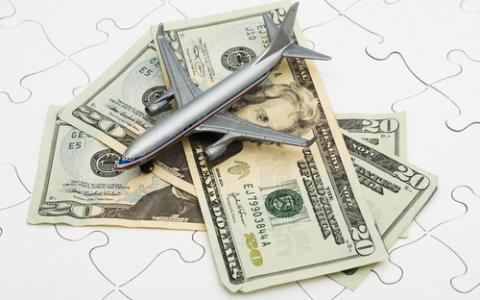 Plane on a pile of money, representing travel expenses.